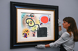 © Licensed to London News Pictures. 29/01/2020. LONDON, UK. A staff member views ''Personnages Et Oiseau Devant Le Soleil'' by Joan Miró, (Est. £1,500,000 - 2,000,000).  Preview of Sotheby's Impressionist & Modern and Surrealist Art sales.  The auction will take place at Sotheby's New Bond Street on 4 and 5 February 2020.  Photo credit: Stephen Chung/LNP