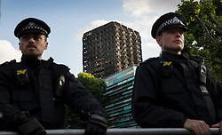 © Licensed to London News Pictures. 16/06/2017. London, UK. Police at a cordon in sight of Grenfell Tower watch as marchers arrive from a protest at Kensington Town Hall. Demonstrators calling for justice for victims had earlier briefly occupied part of Kensington and Chelsea Town Hall. The blaze engulfed the 27-storey building in the early hours of June 13th. Police say 30 people have been killed with 34 still in hospital, 18 of whom are in critical condition. The fire brigade say that they don't expect to find anyone else alive. Photo credit: Peter Macdiarmid/LNP