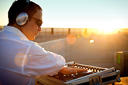 DJ Using Mixing Console at Sunrise