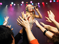 Young Woman Singing in Concert reaching out to fans low angle view