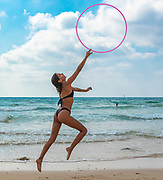 Young woman with a hula hoop on the beach