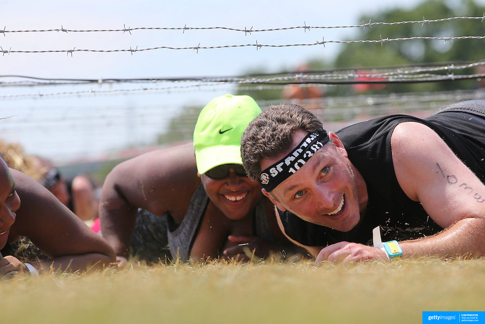 Steve Planeta in action at the barbed wire crawl obstacle during the Reebok Spartan Race. Mohegan Sun, Uncasville, Connecticut, USA. 28th June 2014. Photo Tim Clayton