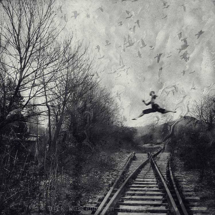 Man jumping over railway tracks