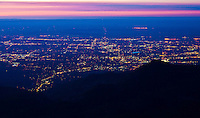 Sunrise over the city lights of Colorado Springs as viewed from the summit of 14,110 ft. Pikes Peak.  Colorado.