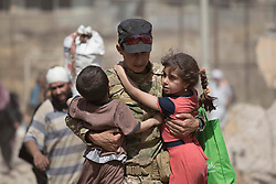 &copy; Licensed to London News Pictures. 15/06/2017. Mosul, Iraq. An Iraqi Army soldier, of 9th Armoured Division, holds two children as they and their family flee from ISIS held West Mosul.<br /> <br /> Despite heavy fighting between the Islamic State and Iraqi Security Forces many civilians have started to leave ISIS territory in West Mosul. Mosul residents, many of whom have been in hiding in their homes since the start of the West Mosul Offensive, often have to run through ISIS sniper and machine gun fire to reach the safety of Iraqi Security Forces positions. Photo credit: Matt Cetti-Roberts/LNP