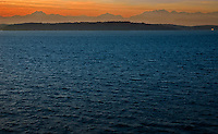 A view at sunset across Puget Sound toward Bainbridge Island with the Olympic Peninsula and Olympic Mountains silhouetted against the warm evening sky.  A Washington State Ferry is in the distance departing Winslow on Bainbridge Island, Washington State.