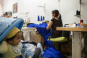 A Bolivian lady working in a immigrant sewing workshop in, São Paulo. Frequently parents have to work with their children in the workshop with them. <br /> <br /> Nearly 90% of the immigrants arriving in São Paulo end up working in the textile industry. <br /> <br /> Today there are about 20,000 sewing shops in São Paulo and 400,000 immigrants working in the clothing sector.