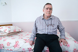 Man with Alzheimer's Disease sitting on his bed at nursing home,