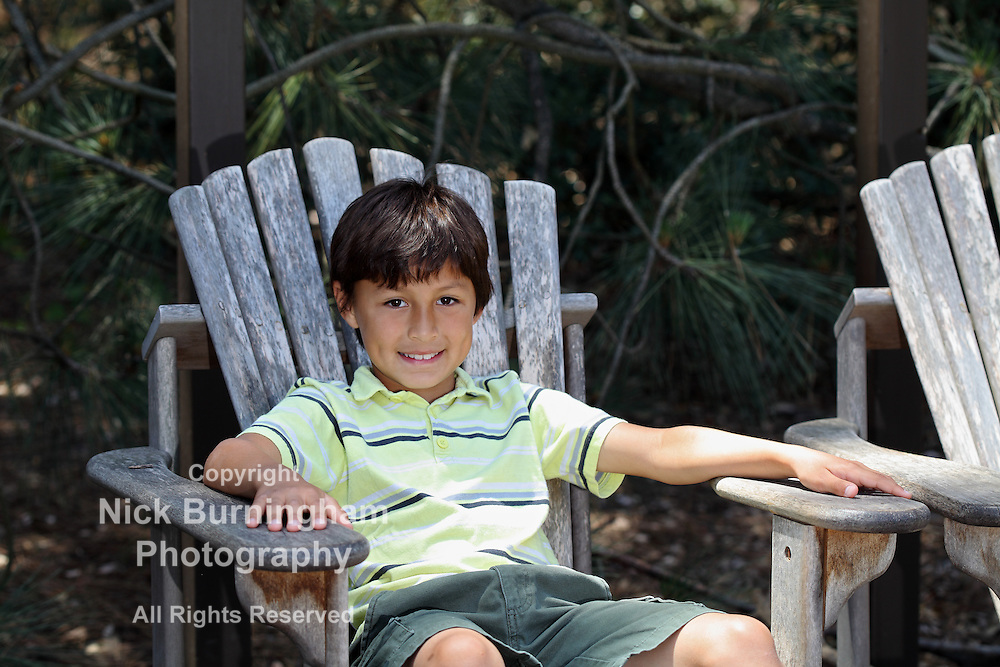 Young boy in the woods sitting on old chair