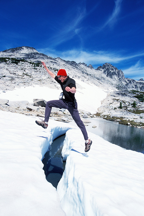 A young man jumping from a snow island in a small lake, Enchanted Lakes Wilderness Area, Washington Cascades, USA.