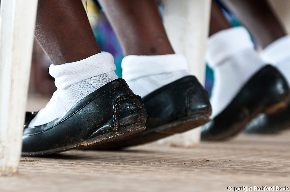 The shoes of school girls up on stage during a competition between schools to see which knew the most about rabies.