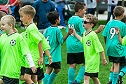 Youth boys soccer teams shake hands after a match.