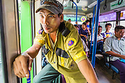 19 JUNE 2013 - YANGON, MYANMAR:  A conductor leans out the open door of a Yangon bus shouting the bus' destination to potential customers. Yangon buses are generally overcrowded and in poor repair but as the economy improves newer, but still used, Japanese and Korean buses are being imported. Hundreds of bus routes criss-cross Yangon, providing the cheapest way of getting around the city. Most fares are less than the equivalent of .20¢ US.  PHOTO BY JACK KURTZ