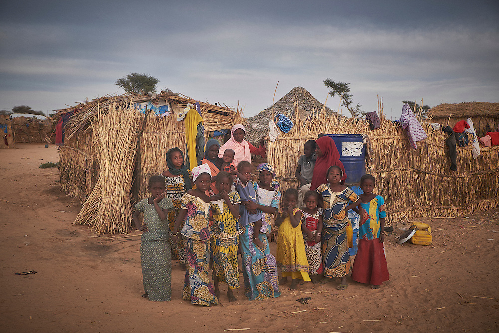 Women and children at a camp of displaced people in the neighbourhood of Chateau, Diffa, Niger on February 13, 2016. The camp is mixed between displaced people from Niger, Nigeria and Chad. They have fled attacks by the militant group Boko Haram on their villages and it's ongoing conflicts with the armies of each country. Caritas undertook a distribution of mosquito nets, cooking pots, sleeping covers, hygiene kits, clothes and cash transfers to the displaced. 228 households received support from Caritas among an estimated 1500 households in the  vicinity of Chateau. There is still great need. There is no school system in place for the children and the housing is not adequate for many as more people arrive each day escaping hostilities.