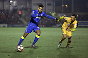 AFC Wimbledon striker Lyle Taylor (33) battles for possesion during the The FA Cup third round replay match between AFC Wimbledon and Sutton United at the Cherry Red Records Stadium, Kingston, England on 17 January 2017. Photo by Matthew Redman.
