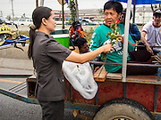 21 FEBRUARY 2014 - KHLONG CHIK, PHRA NAKHON SI AYUTTHAYA, THAILAND: A Thai police woman presents roses to farmers protesting against the government on Highway 32. About 10,000 Thai rice farmers, traveling in nearly 1,000 tractors and farm vehicles, blocked Highway 32 near Bang Pa In in Phra Nakhon Si Ayutthaya province. The farmers were traveling to the airport in Bangkok to protest against the government because they haven't been paid for rice the government bought from them last year. The farmers turned around and went home after they met with government officials who promised to pay the farmers next week. This is the latest blow to the government of Yingluck Shinawatra which is confronting protests led by anti-government groups, legal challenges from the anti-corruption commission and expanding protests from farmers who haven't been paid for rice the government bought.    PHOTO BY JACK KURTZ