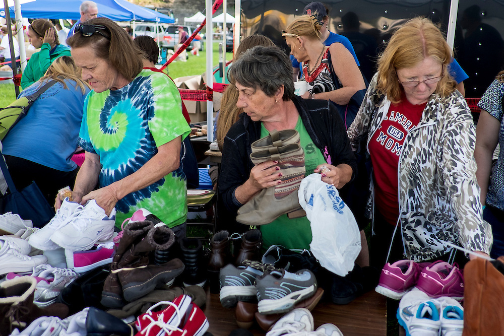 A local church offered one free pair of new shoes to patients at the 16th annual Remote Area Medical (RAM), clinic in Wise, Virginia, U.S., on Friday, July 17, 2015. RAM is a nonprofit that delivers free medical care to people living in rural areas. On RAM's first day it took in over 1,600 patients, setting an opening day record. By noon on Saturday, RAM had taken in another 1,000 patients. One woman's life may have been saved on Friday after women's health physicians determined she had a dangerous ectopic (tubal) pregnancy. She was taken to an area hospital for further care. In recent years, 2,500 to 3,000 people have sought care at this clinic at the fairgrounds. Photographer: Pete Marovich/Bloomberg