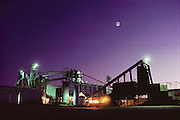 The Harris Ranch cattle feed lot, the Harris Feeding Company, in Coalinga, California. California's largest feed lot with up to 100,000 head of cattle. The highly automated feed mill at dusk with a full moon above it. Coalinga, California. San Joaquin Valley. USA.[[From the company: THE HARRIS FARMS GROUP OF COMPANIES. Harris Farms, Inc. is one of the nation's largest, vertically integrated family owned agribusinesses]].
