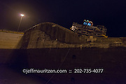 "A ""mule"" assists a shipping vessel to transit the Gatun Locks in the Panama Canal at night."