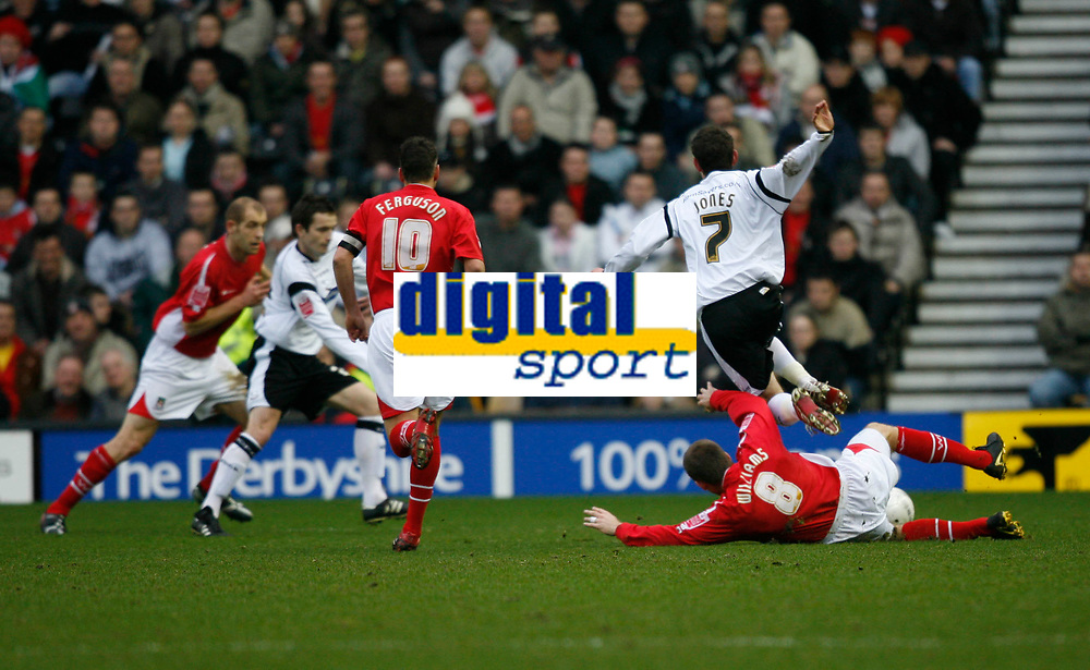 David Jones of Derby County (white no7) is brought down by Wrexham's Danny Williams (red, no 8)
