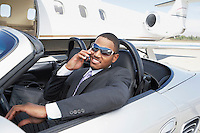 Man sitting in Convertible near private jet talking on mobile