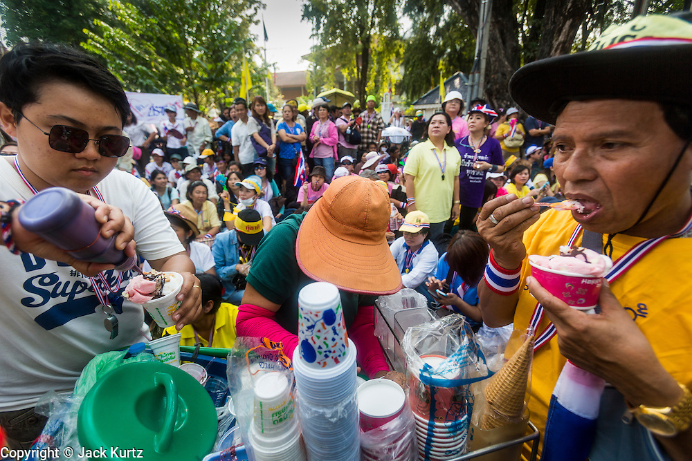 "09 DECEMBER 2013 - BANGKOK, THAILAND:  Thai anti-government protestors buy ice cream from a street vendor while they wait to get into Government House in Bangkok. Thai Prime Minister Yingluck Shinawatra announced she would dissolve the lower house of the Parliament and call new elections in the face of ongoing anti-government protests in Bangkok. Hundreds of thousands of people flocked to Government House, the office of the Prime Minister, Monday to celebrate the collapse of the government after Yingluck made her announcement. Former Deputy Prime Minister Suthep Thaugsuban, the organizer of the protests, said the protests would continue until the ""Thaksin influence is uprooted from Thailand."" There were no reports of violence in the protests Monday.     PHOTO BY JACK KURTZ"