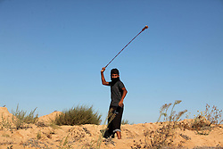September 30, 2016 - Bureij, Gaza Strip, Palestinian Territory - A Palestinian protester uses a slingshot to hurl stones toward Israeli security forces during clashes near the border between Israel and Central Gaza Strip east of Bureij on Sep. 30, 2016  (Credit Image: © Ashraf Amra/APA Images via ZUMA Wire)