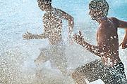 Men running and playing in lake.