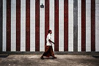 A man in traditional dress walks past the outer walls of Sri Veeramakaliamman Temple in Little India, Singapore.