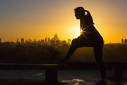 A jogger stretches as day breaks over London's skyline, seen from Primrose Hill, to the north of the city. London, November 13 2018.