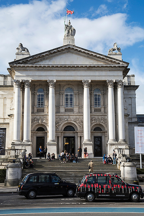 Two taxis parked outside Tate Britain, a major art gallery in London displaying British Art, A crowd of people are sitting on the steps leading to the gallery.