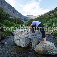 woman doiong yoga over small mountain creek
