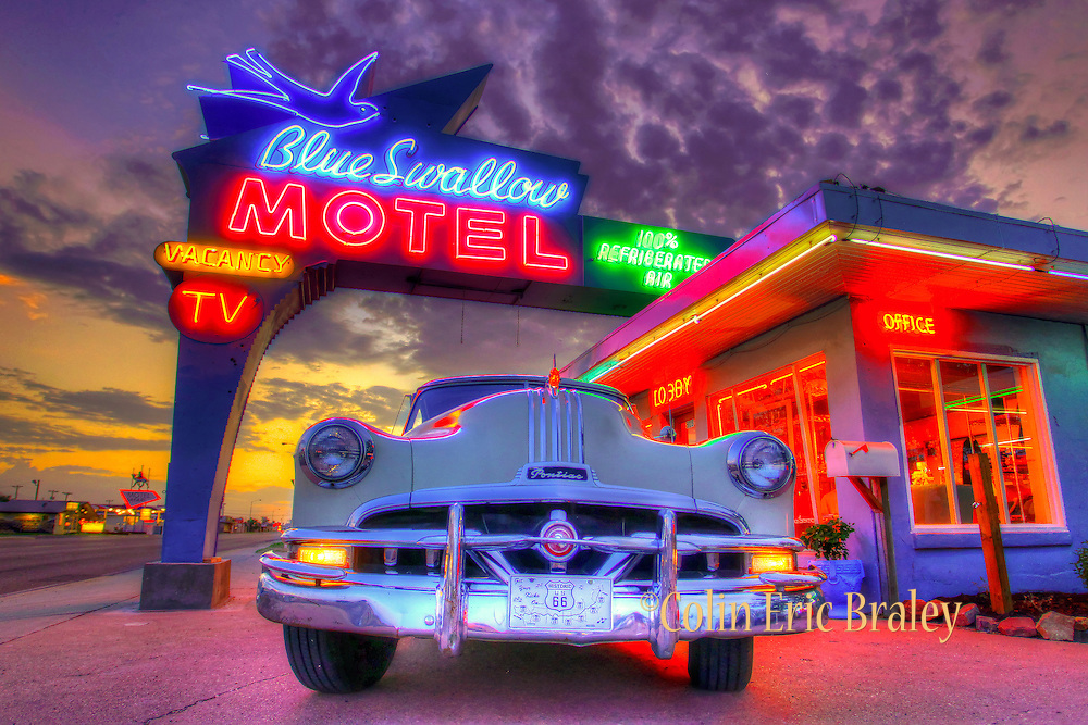Route 66-New Mexico- A 1951 Pontiac Eight is illuminated by the glow of a New Mexico sunset and the neon lights of the Art Deco-styled Blue Swallow Motel along Route 66 in the town of Tucumcari. Photo by Colin E Braley