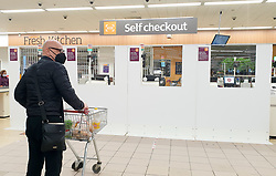 © Licensed to London News Pictures. 05/05/2020. London, UK. A shopper wearing a face covering waits at a self checkout in Sainsbury's supermarket. <br /> Partitions are installed in-between checkouts at Sainsbury's supermarket in north London to maintain the 2m distance rule to avoid the spread of COVID-19.  Photo credit: Dinendra Haria/LNP