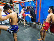 "11 DECEMBER 2014 - THONBURI, BANGKOK, THAILAND:  The Kanisorn boxing gym is a small gym along the Wong Wian Yai - Samut Sakhon train tracks. Young people from the nearby communities come to the gym to learn Thai boxing. Muay Thai (Muai Thai) is a Thai fighting sport that uses stand-up striking along with various clinching techniques. It is sometimes known as ""the art of eight limbs"" because it is characterized by the combined use of fists, elbows, knees, shins, being associated with a good physical preparation that makes a full-contact fighter very efficient. Muay Thai became widespread internationally in the twentieth century, when practitioners defeated notable practitioners of other martial arts. A professional league is governed by the World Muay Thai Council. Muay Thai is frequently seen as a way out of poverty for young Thais and Muay Thai camps and schools are frequently crowded. Muay Thai professionals and champions are often celebrities in Thailand.    PHOTO BY JACK KURTZ"