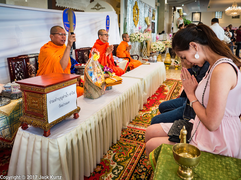 "14 FEBRUARY 2017 - BANGKOK, THAILAND:  Buddhist monks bless a couple's marriage during a mass wedding in the Bang Rak district in Bangkok. Bang Rak is a popular neighborhood for weddings in Bangkok because it translates as ""Village of Love."" (Bang translates as village, Rak translates as love.) Hundreds of couples get married in the district on Valentine's Day, which, despite its Catholic origins, is widely celebrated in Thailand.     PHOTO BY JACK KURTZ"