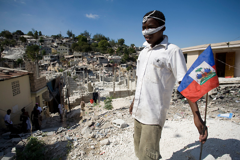 A boy, with fabric tied across his nose to fight the smell of the dead, holds a Haitian flag in a heavily earthquake damaged neighborhood. Pettionville, Haiti. 1/15/2010.  Photo by Ben Depp