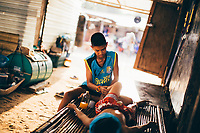 Boonsong Samrong, a young Muay Thai fighter, has his legs and muscles massages by his older brother before a fight.