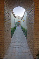 View through archway down path to French doors of luxury home