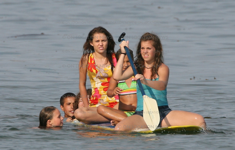 MALIBU, CALIFORNIA - FRIDAY 11TH JUly 2008 NON EXCLUSIVE: Miley Cyrus shooting beach scenes for her movie 'Hannah Montana'. Cyrus was joined on set by her father Billy Ray Cyrus And Ugly Betty star Vanessa Williams. Miley played in the Ocean with a pal during a break in filming and then again later paddling on a surfboard while her Dad finished shooting his scenes. Photograph: On Location News. Sales: Eric Ford 1/818-613-3955 info@OnLocationNews.com