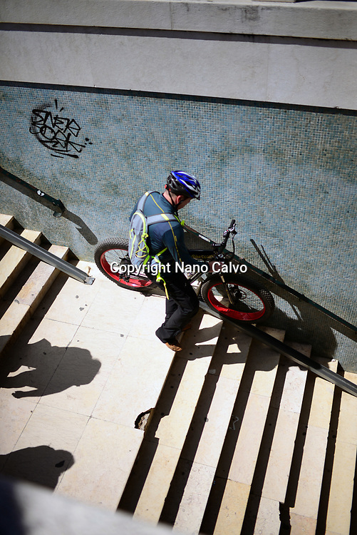 Man walking down stairs with fat bike, Belem, Lisbon