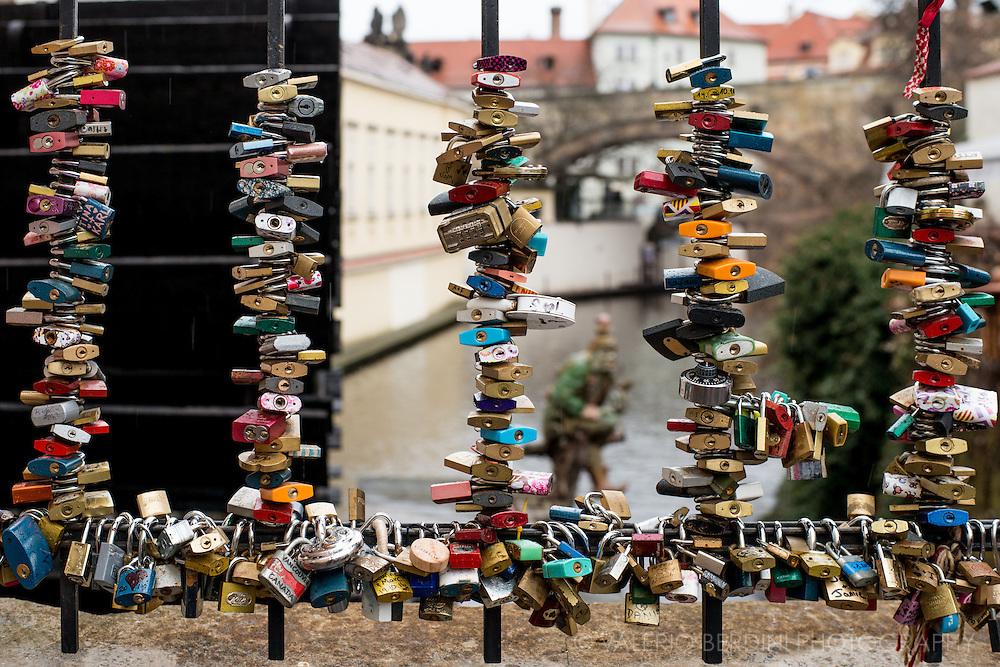 Locks left on a gate on Lover's bridge, along Certovka canal in Kampa