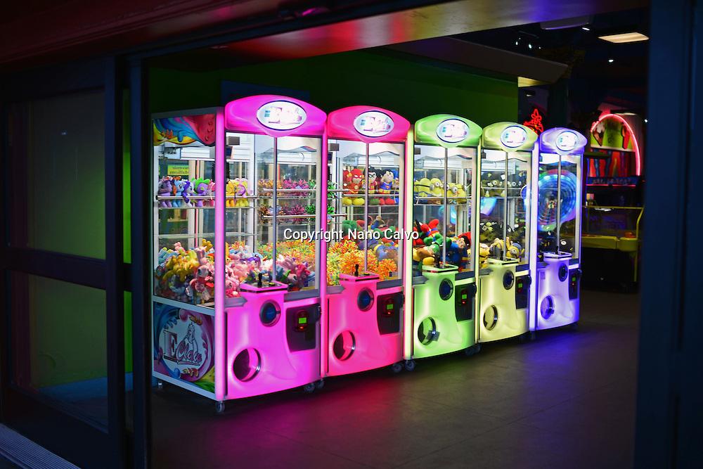 Claw machines in different neon colours, Santa Cruz, California.