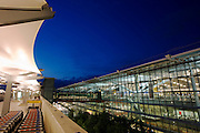 Early evening exterior of glass walls and glowing architecture of Heathrow Airport's Terminal 5, seen from departures level