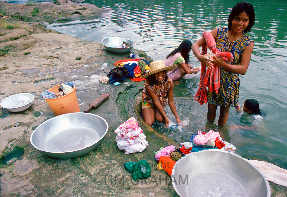 Girls washing clothes in a river, Philippines