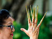 03 APRIL 2018 - CHIANG MAI, THAILAND: A woman wearing traditional brass finger extensions rehearses a traditional Songkran dance. Songkran is the traditional Thai New Year festival and is celebrated April 13-15. The holiday is best known for raucous water fights but it is an important cultural and religious holiday.       PHOTO BY JACK KURTZ
