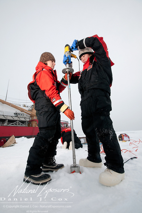 Cristina Galvan and Brenna McConnell taking ice core samples from the ice of the Arctic Ocean.