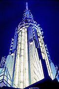 The illuminated, rocketship-like, Art Deco spire of the Empire State Building with broadcasting antennas against a deep blue, night sky