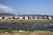 A poluted water stream runs by homes in an area where much of the world's electronic waste _ from cell phone chargers to mainframe computers _ ends up in Guiyu and other small towns like it in eastern China, Thursday March 16, 2006. Workers, many of them poorly paid migrants strip, smash and melt down circuit boards, mainly to extract the copper and other precious metals inside. The business has created massive pollution from leaded glass and other toxic materials. A water sample taken from the site revealed lead levels 2,400 times higher than the World Health Organization's limit for drinking water.