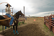 Cowgirl header competes in team roping at rodeo in Wilsall Montana